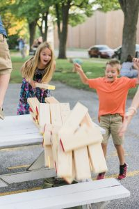 Kids playing giant jenga as the tower falls at the wedding reception